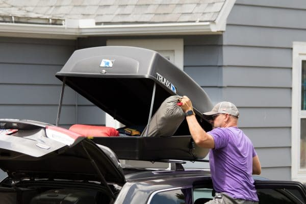Man filling up an 18 cu ft carrier with camping equipment